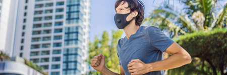BANNER, LONG FORMAT Man runner wearing medical mask. Running in the city against the backdrop of the city. Coronavirus pandemic Covid-19. Sport, Active life in quarantine surgical sterilizing face mask protection. Outdoor run on athletics track in Corona Outbreak