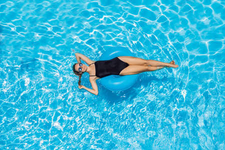 Woman sitting in a swimming pool on a ring pool float in sunglasses