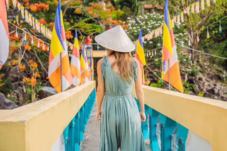 Young woman tourist in a traditional Vietnamese hat travels to Vietnam