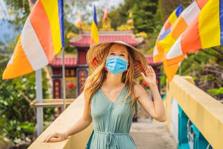 Young woman tourist in medical mask in a traditional Vietnamese hat travels to Vietnam. Tourists fear a coronovirus and wear a medical mask