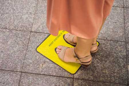 Legs and feet of a person waiting in line and standing inside yellow floor sign keep your distance with social distancing measures pandemic outbreak
