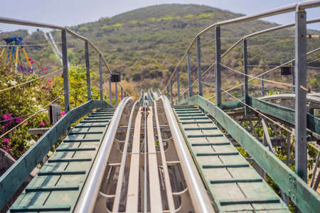 Rail downhill on a trolley, Point of view during a ride on Alpine Coaster on rails Standard-Bild - 150218964