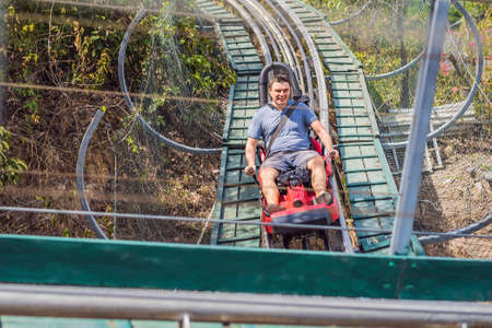Man on Rail downhill on a trolley, Point of view during a ride on Alpine Coaster on rails Standard-Bild - 148954061