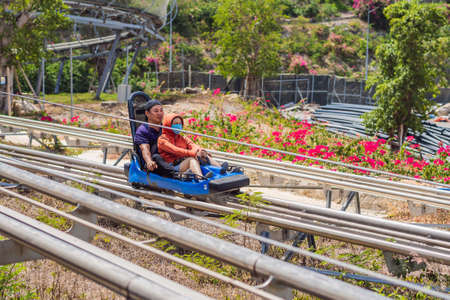 Vietnam, Nha Trang, 24.05.2020: People in medical masks after an epidemic of coronovirus on Rail downhill on a trolley, Point of view during a ride on Alpine Coaster on rails