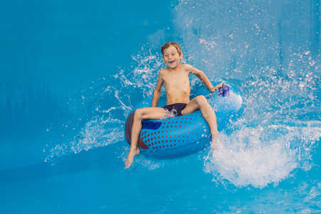 Boy on a pool float on artificial waves in a water park