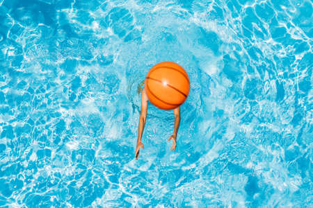 Man play in the pool with a beach ball