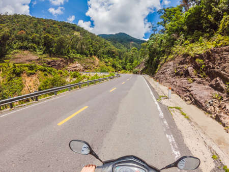 Motorcyclist rides on a serpentine road in cloudy weather. Vietnam, Dalat. 免版税图像 - 150332302