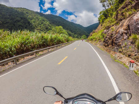 Motorcyclist rides on a serpentine road in cloudy weather. Vietnam, Dalat. 免版税图像 - 150332562