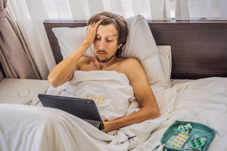 Male patient is sick while lying in his bed and calls an online doctor through a gadget