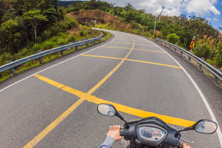 Motorcyclist rides on a serpentine road in cloudy weather. Vietnam, Dalat. 免版税图像 - 150347186
