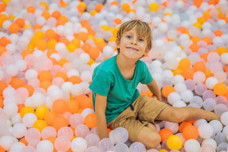 Child playing in ball pit. Colorful toys for kids. Kindergarten or preschool play room. Toddler kid at day care indoor playground. Balls pool for children. Birthday party for active preschooler