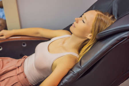 Beautiful young woman relaxing on the massage chair in airport or in the mall Stock Photo