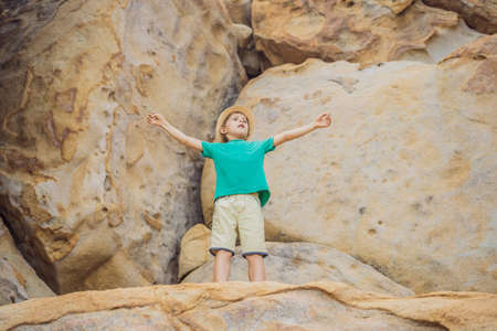 Young boy climbing on a rock, vacation concept