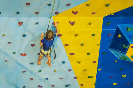 6 years old child climbing on a wall in a climbing center