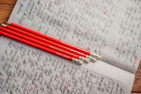 Vietnam, Nha Trang, 14.07.2020: IELTS red pencils and essay notebook for the English exam