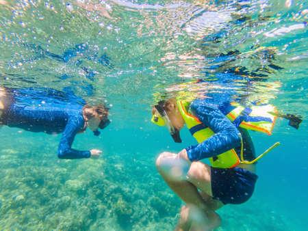 Child wearing snorkeling mask diving underwater Stock Photo