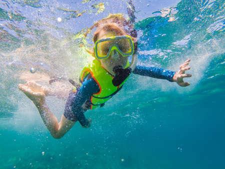 Child wearing snorkeling mask diving underwater