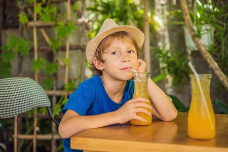 cute little boy drinking orange juice in cafe
