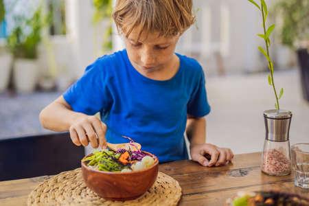 Boy eating Poke bowl with shrimp, corn, avocado, ginger and mushrooms