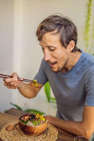 Man eating Poke bowl with shrimp, corn, avocado, ginger and mushrooms