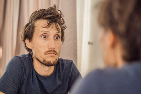 Extremly tired young man looking at himself in the mirror, home alone. self-isolation at home, quarantine due to pandemic COVID 19. Mental health problems in self-isolation at home