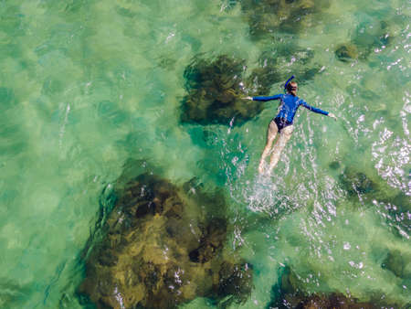 The woman is snorkeling among the corals. View from the drone