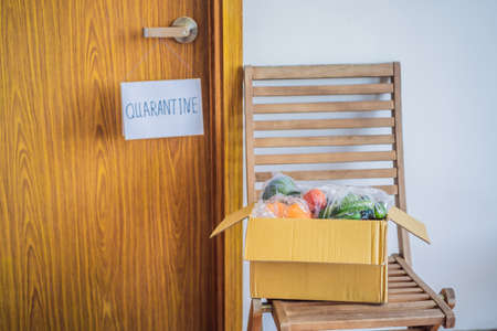 Home delivery food during virus outbreak, coronavirus panic and pandemics. Stay safe Coronavirus covid-19 quarantine sign at Front door, quarantine sign at home Stock Photo