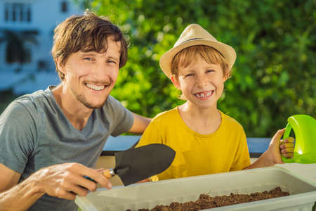 Dad and son is doing gardening on his balcony. Natural development for children