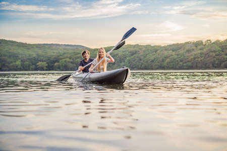 Man and woman swims on kayak in the sea on background of island. Kayaking concept.Kayaking concept with family of father mother at sea