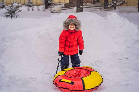 Child having fun on snow tube. Boy is riding a tubing. Winter fun for children