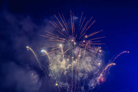 Beautiful colorful holiday fireworks in the evening sky with majestic clouds