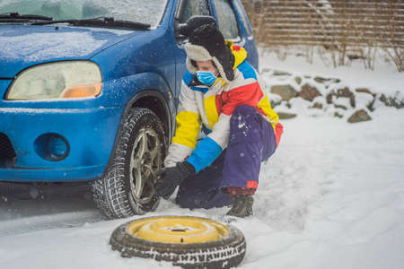 Winter accident on the road. A man changes a wheel during a snowfall wear medical masks due to the COVID-19 coronavirus. Winter problems