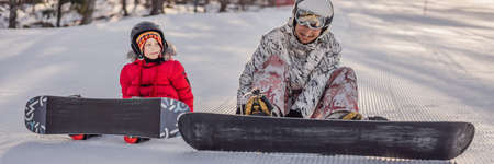 Dad teaches son snowboarding. Activities for children in winter. Childrens winter sport. Lifestyle BANNER, LONG FORMAT 免版税图像