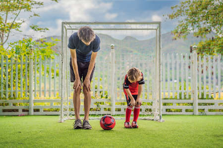 Little cute kid boy in red football uniform and his trainer or father playing soccer, football on field, outdoors. Active child making sports with kids or father, Smiling happy boy having fun in summer.