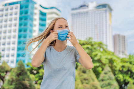 Improper wearing of mask concept. Woman scratching his nose under the mask, touches the mask