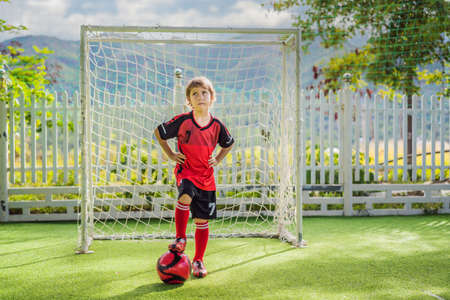 Little cute kid boy in red football uniform playing soccer, football on field, outdoors. Active child making sports with kids or father, Smiling happy boy having fun in summer Archivio Fotografico