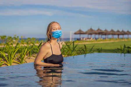 Woman wearing a medical mask during COVID-19 coronavirus relaxing in infinity swimming pool looking at view
