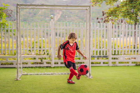 Little cute kid boy in red football uniform playing soccer, football on field, outdoors. Active child making sports with kids or father, Smiling happy boy having fun in summer