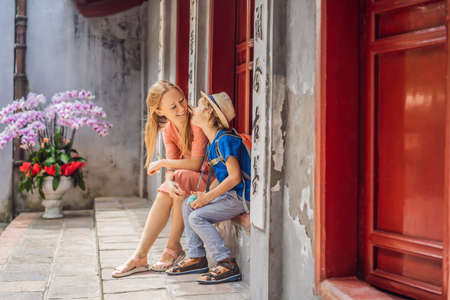 tourists mom and son on background of Temple Ngoc Son in Hanoi, Vietnam.Temple of Literature is also called temple of Confucius. Vietnam reopens after coronavirus quarantine COVID 19