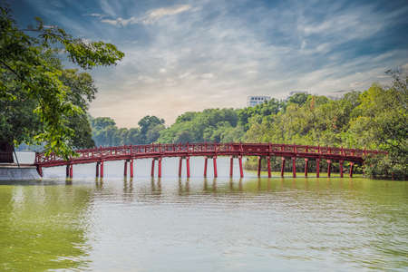 The Red Bridge in public park garden with trees and reflection in the middle of Hoan Kiem Lake in Downtown Hanoi. Urban city at sunset, Vietnam. Cityscape background