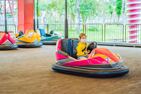 Boy wearing a medical mask during COVID-19 coronavirus having a ride in the bumper car at the amusement park