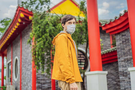 traveler in medical mask stopped on the street and looking at the Japanese, Chinese, Korean, Vietnamese traditional building. Tourists travel in Asia after the coronavirus epidemic