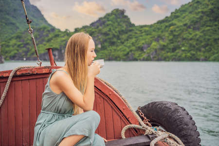 Attractive woman in a dress is drinking coffee, traveling by boat in Halong Bay. Vietnam. Travel to Asia, happiness emotion, summer holiday concept. Picturesque sea landscape. Ha Long Bay, Vietnam
