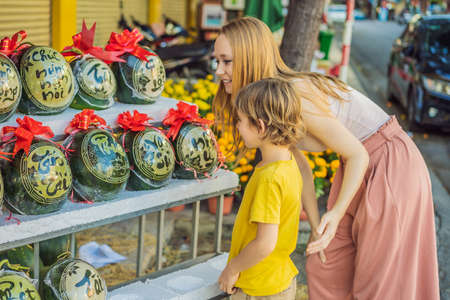Mom and son tourists look at Watermelons with festive engraving on Tet Eve. Tet is Lunar New Year and celebrated during four days in Vietnam