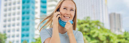 Improper wearing of mask concept. Woman wearing mask wrong, took off mask while talking on the phone BANNER, LONG FORMAT