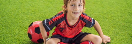 BANNER, LONG FORMAT Little cute kid boy in red football uniform playing soccer, football on field, outdoors. Active child making sports with kids or father, Smiling happy boy having fun in summer Stock Photo