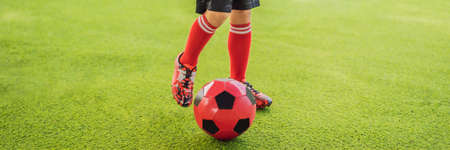 BANNER, LONG FORMAT Little cute kid boy in red football uniform playing soccer, football on field, outdoors. Active child making sports with kids or father, Smiling happy boy having fun in summer
