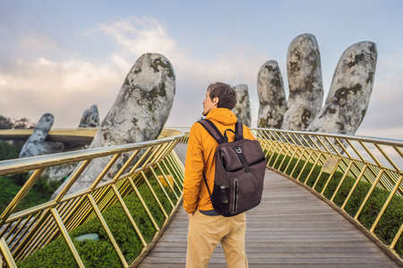 Young man tourist at Famous tourist attraction - Golden bridge at the top of the Ba Na Hills, Vietnam
