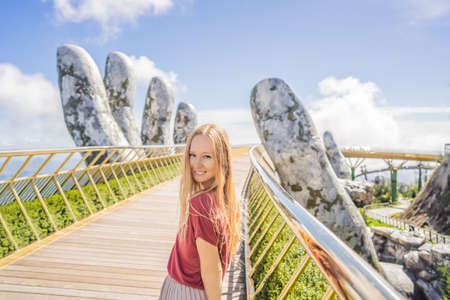 Young woman tourist at Famous tourist attraction - Golden bridge at the top of the Ba Na Hills, Vietnam