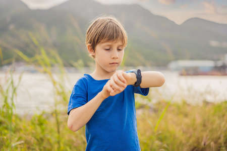 Boy uses kids smart watch outdoor against the background of the garden